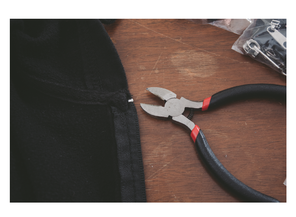 pliers and top zipper stop on brown table