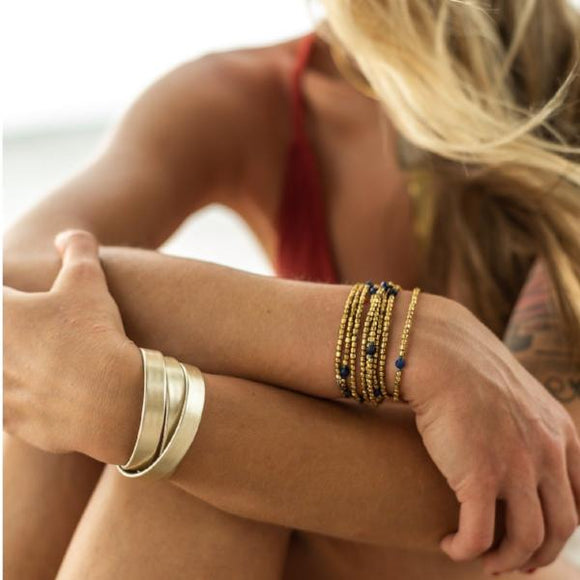 Amy Margaret model photo wearing Tiana wide wrap bracelet in metallic gold