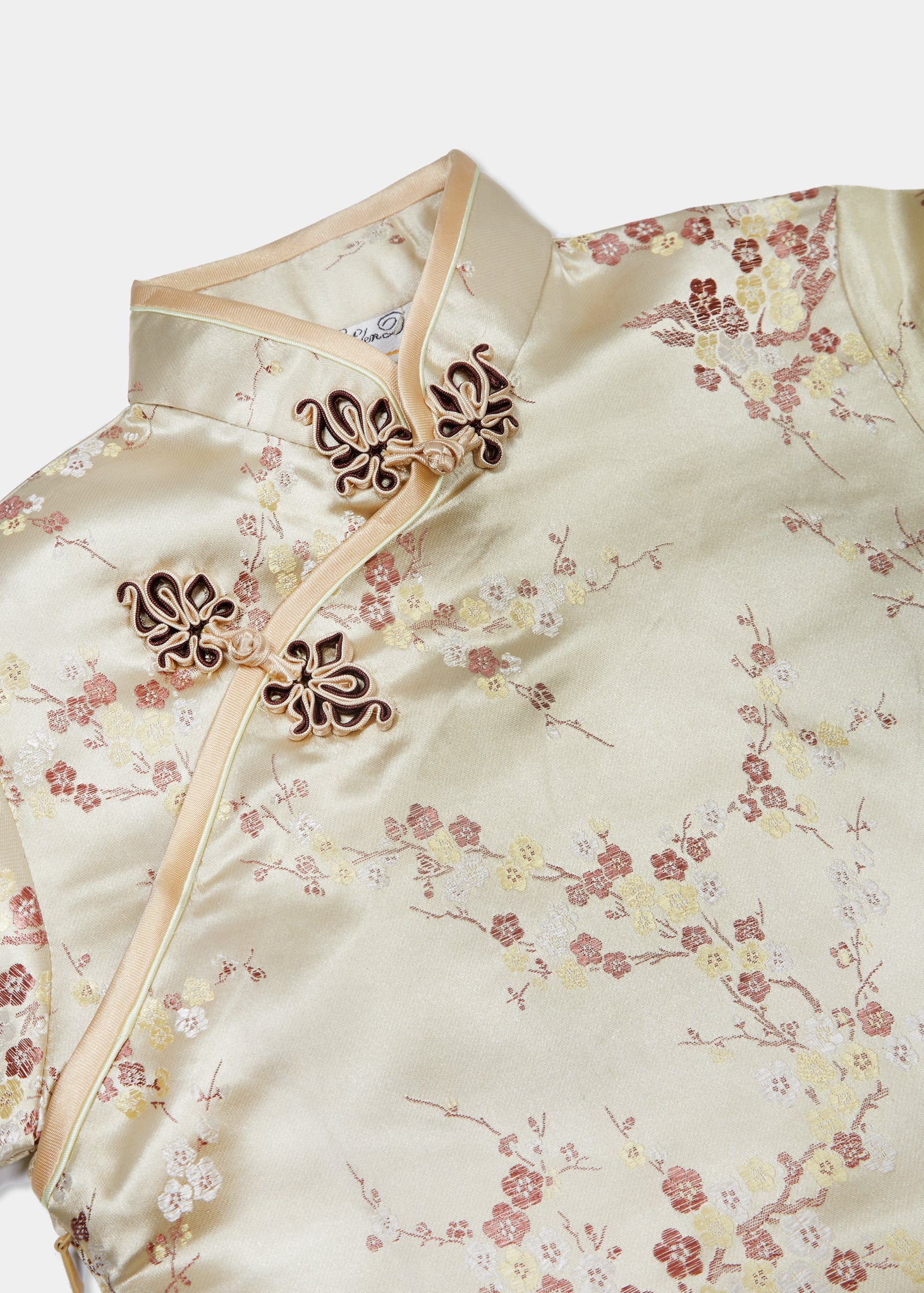 Bound edge mandarin collar and aysmmetric fastening which closes with hand stitched flower and knot frog fastenings in an accent shade. Short sleeves, side zip, curved hem into modest side splits with contrast binding and accent piping.