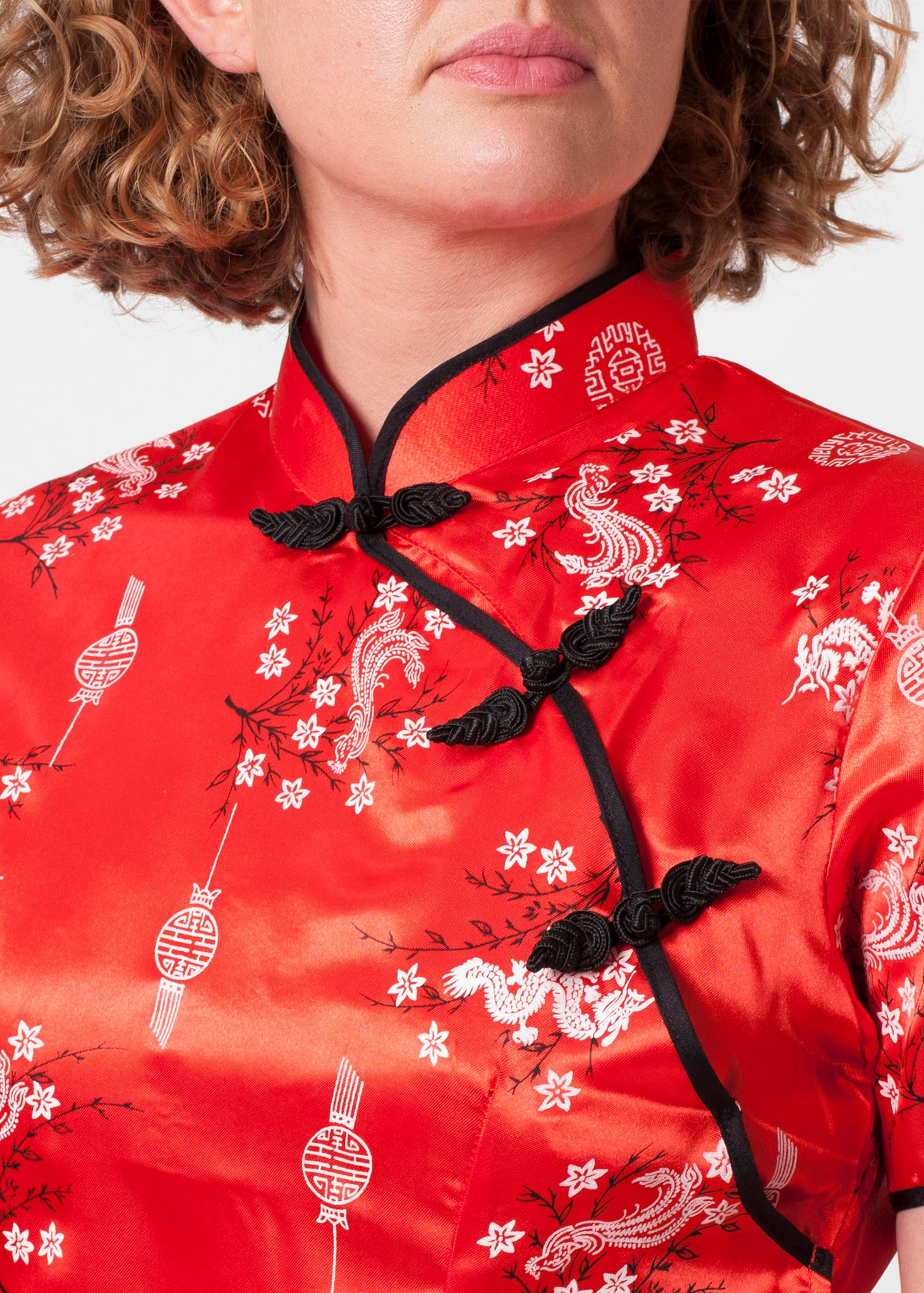 Bound edge mandarin collar and aysmmetric fastening which closes with contrasting flower and knot frog fastenings