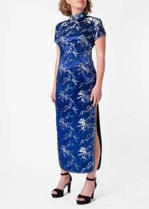 The Cheongsam or Qipao, is a feminine body-hugging dress with distinctive Chinese features of mandarin collar, side splits and flower and knot frog fastenings. Manufactured in high quality silk/rayon brocade which has a beautiful lustre. In blue with a silver cherry blossom design - a symbol of female beauty and love.