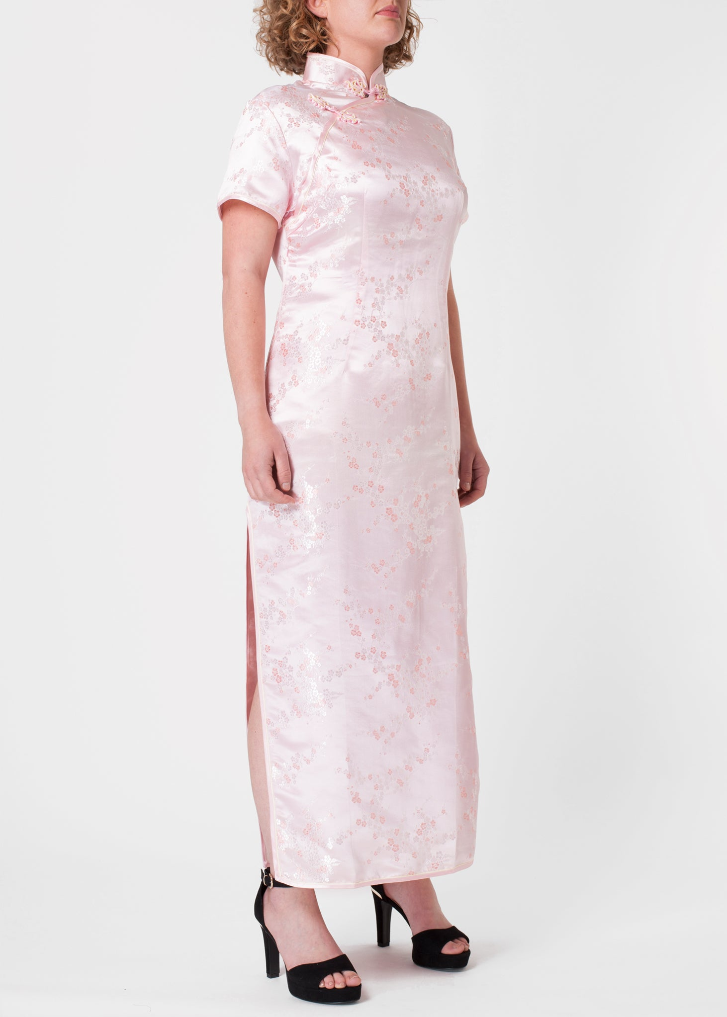 The Cheongsam or Qipao, is a feminine body-hugging dress with distinctive Chinese features of mandarin collar, side splits and hand stitched flower and knot frog fastenings. Manufactured in authentic high quality silk/rayon brocade in a beautiful subtle pink cherry blossom design - a symbol of female beauty and love
