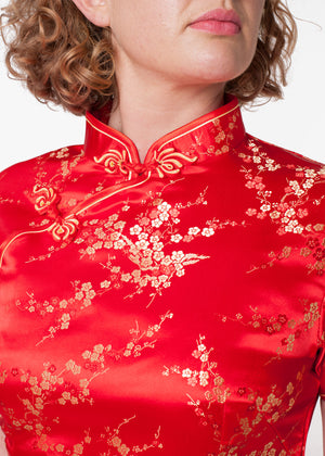 Bound edge mandarin collar dress with aysmmetric fastening which closes with hand stitched flower and knot frog fastenings in an accent shade