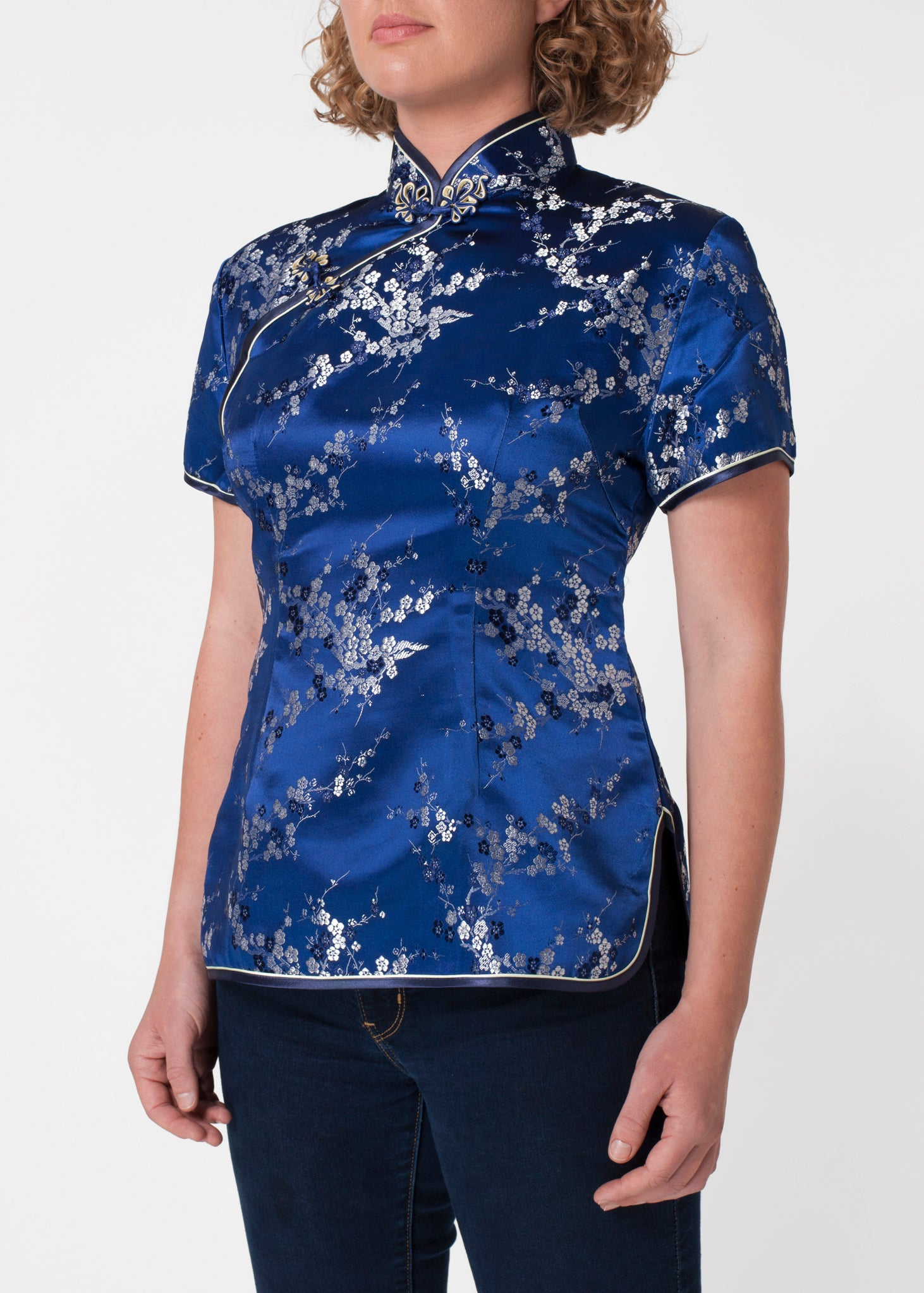 Traditional Chinese blouse in Cheongsam or Qipao style with distinctive Chinese features of mandarin collar, hand stitched flower and knot frog fastenings and side zip. Manufactured in authentic high quality silk/rayon brocade in rich blue and silver cherry blossom design - a symbol of female beauty and love.
