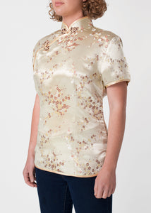 Traditional Chinese blouse in Cheongsam or Qipao style with distinctive Chinese features of mandarin collar, hand stitched flower and knot frog fastenings and side zip. Manufactured in authentic high quality silk/rayon brocade in a classic gold cherry blossom design - a symbol of female beauty and love.