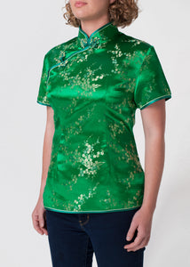 Traditional Chinese blouse in Cheongsam or Qipao style with distinctive Chinese features of mandarin collar, hand stitched flower and knot frog fastenings and side zip. Manufactured in authentic high quality silk/rayon brocade in a emerald green with gold cherry blossom design - a symbol of female beauty and love.