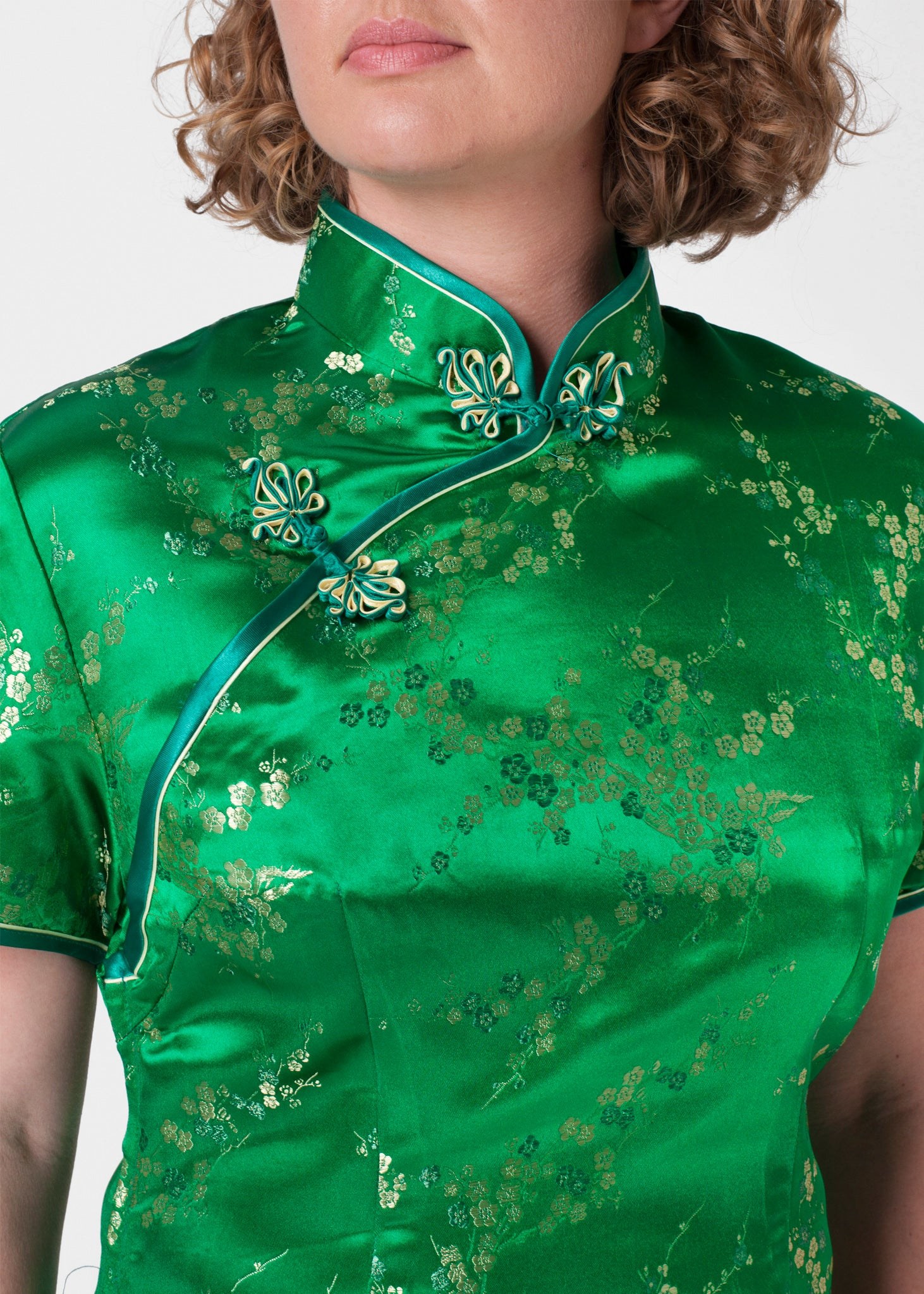 Bound edge mandarin collar and aysmmetric fastening which closes with hand stitched flower and knot frog fastenings in an accent shade. Open ended side zip and press studs