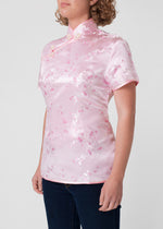 Traditional Chinese blouse in Cheongsam or Qipao style with distinctive Chinese features of mandarin collar, hand stitched flower and knot frog fastenings and side zip. Manufactured in authentic high quality silk/rayon brocade in a delicate shell pink cherry blossom design - a symbol of female beauty and love.