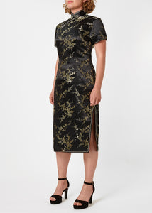 The Cheongsam or Qipao, is a feminine body-hugging dress with distinctive Chinese features of mandarin collar, side splits and hand stitched flower and knot frog fastenings. Manufactured in authentic high quality silk/rayon brocade in black with gold cherry blossom design - a symbol of female beauty and love.