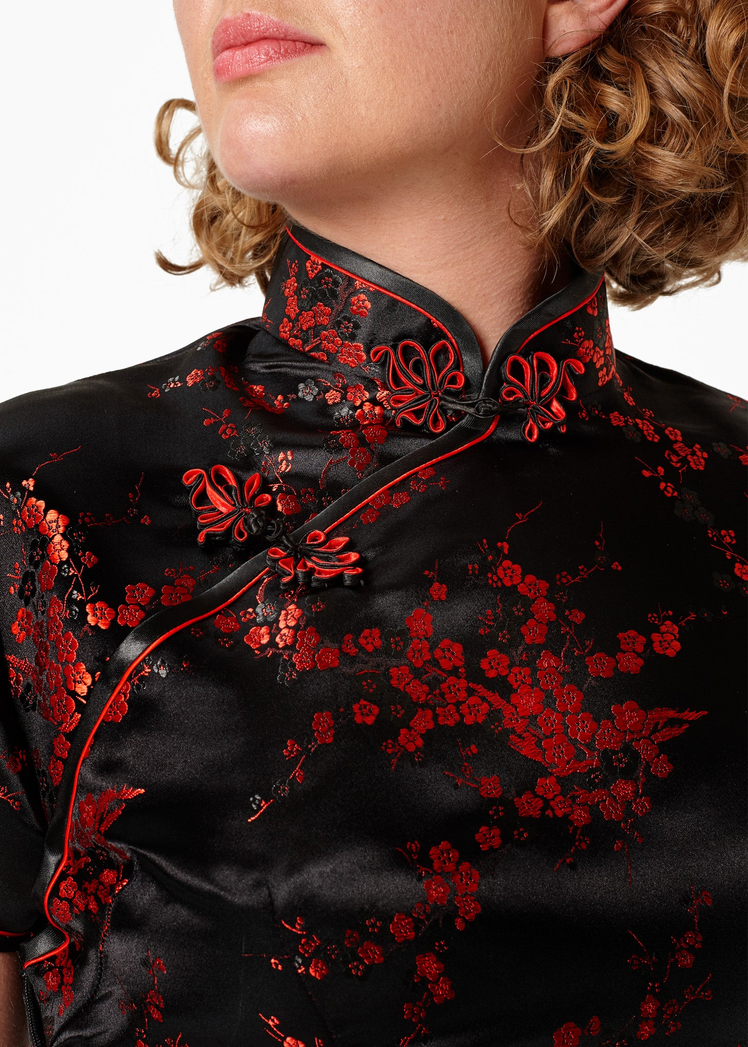 Bound edge mandarin collar and aysmmetric fastening which closes with hand stitched flower and knot frog fastenings in an accent shade