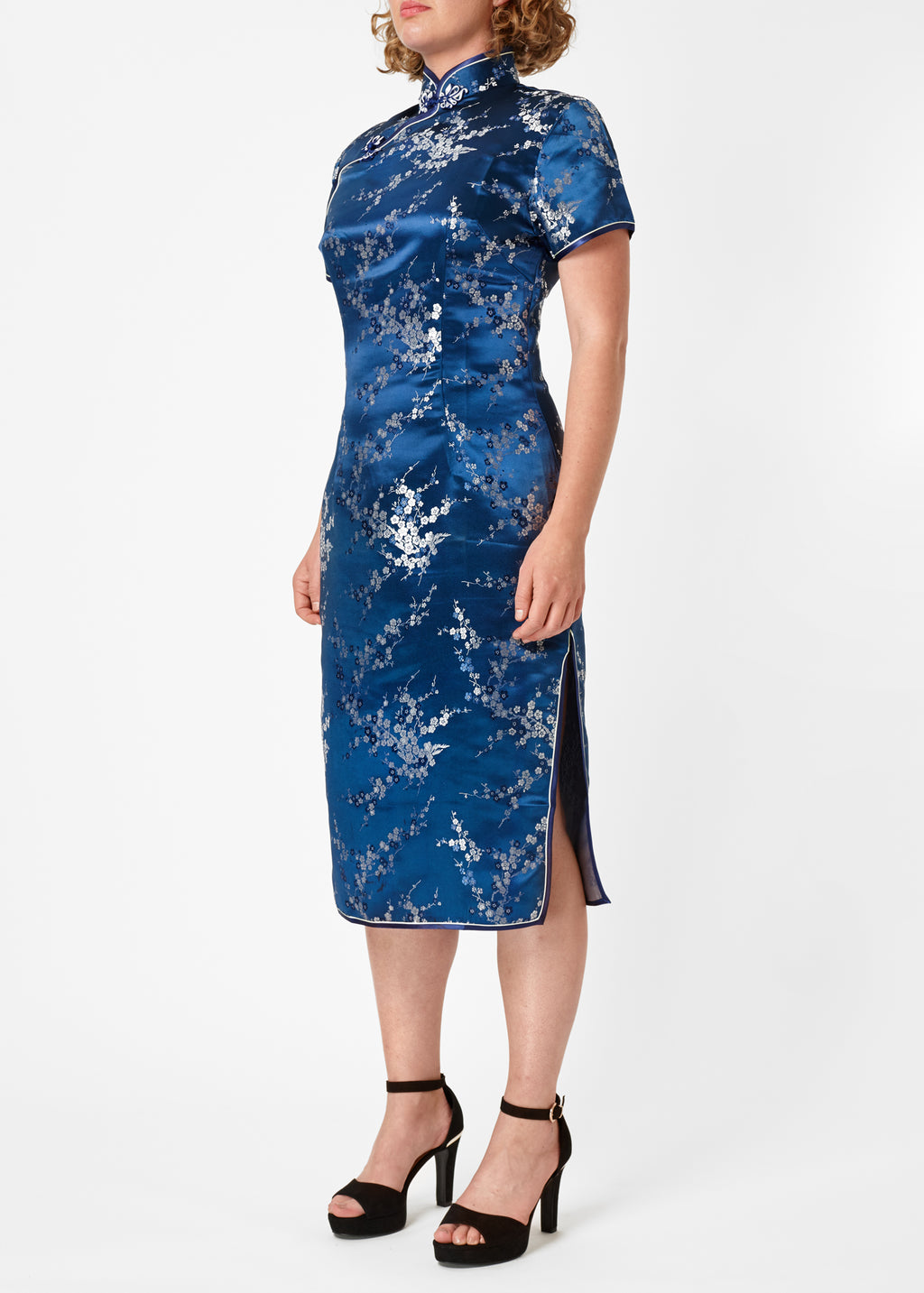 The Cheongsam or Qipao, is a feminine body-hugging dress with distinctive Chinese features of mandarin collar, side splits and hand stitched flower and knot frog fastenings. Manufactured in authentic high quality silk/rayon brocade in a rich blue with silver cherry blossom design - a symbol of female beauty and love.