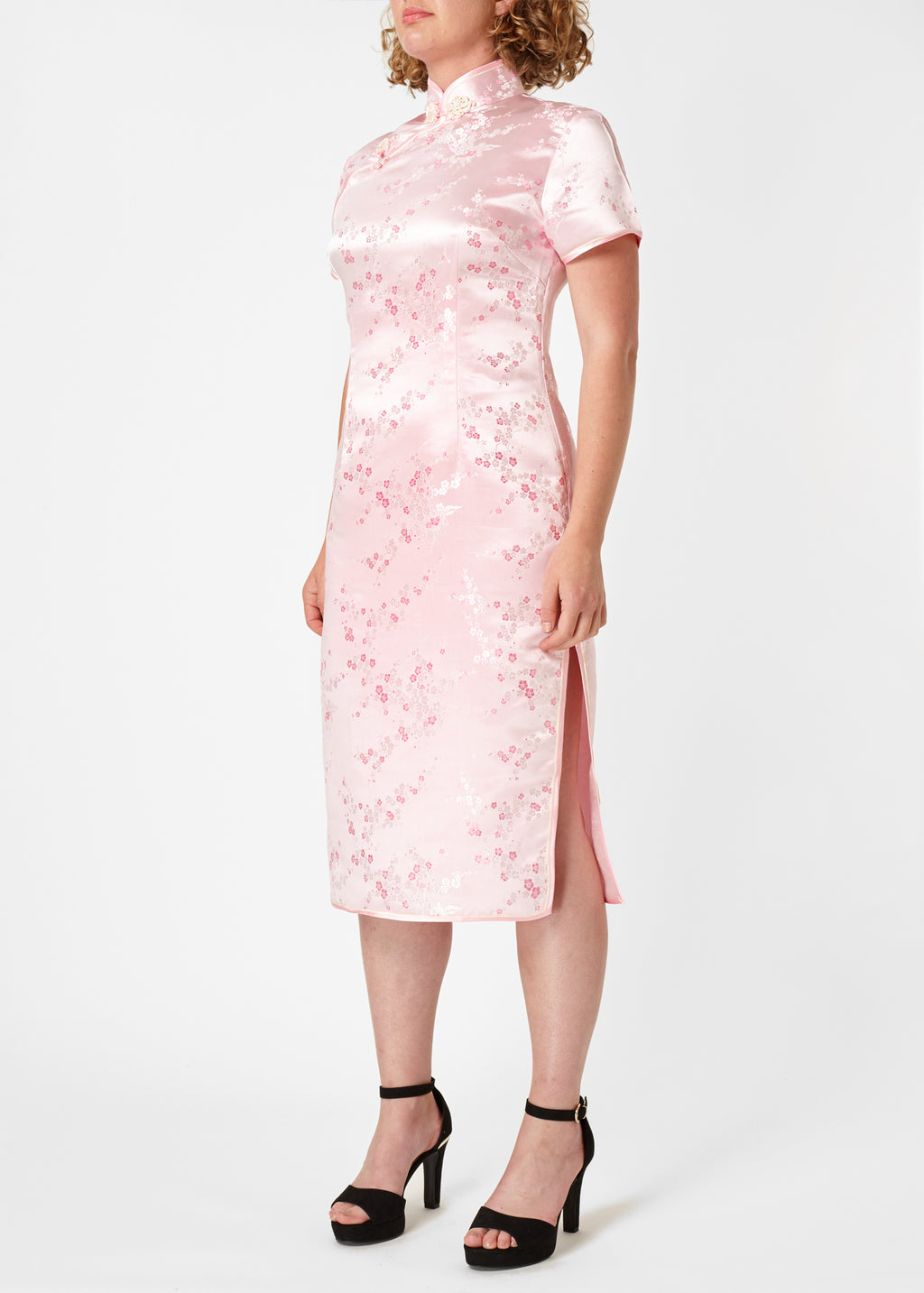 The Cheongsam or Qipao, is a feminine body-hugging dress with distinctive Chinese features of mandarin collar, side splits and hand stitched flower and knot frog fastenings. Manufactured in authentic high quality silk/rayon brocade in a beautiful subtle pink cherry blossom design - a symbol of female beauty and love.