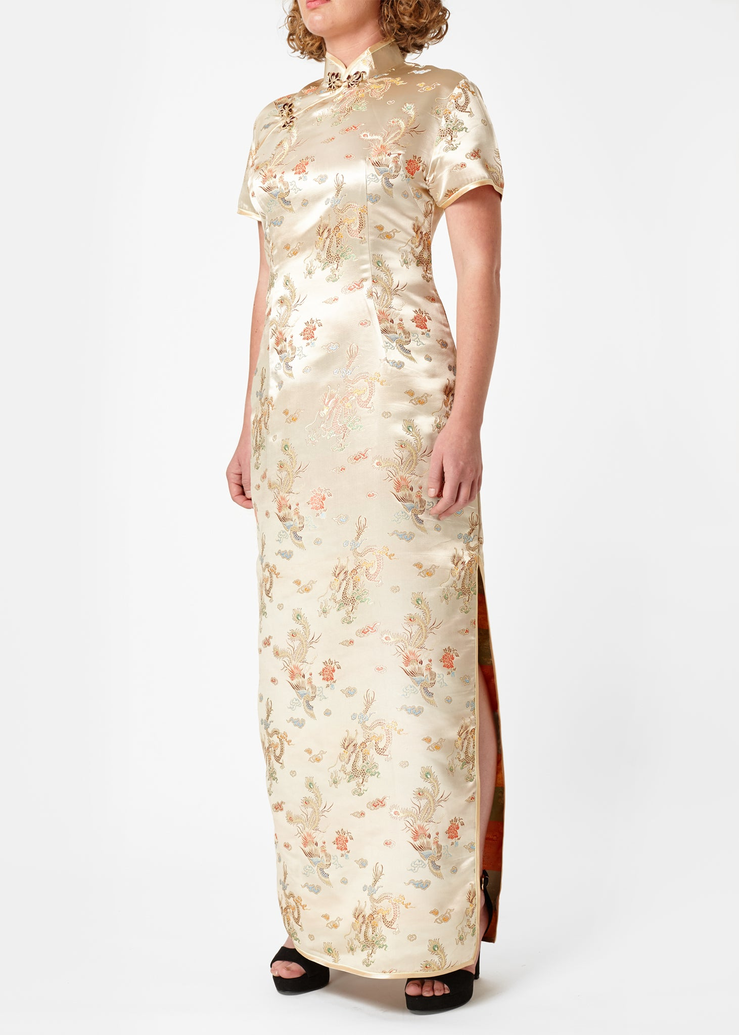 The Cheongsam or Qipao, is a feminine body-hugging dress with distinctive Chinese features of mandarin collar, side splits and hand stitched flower and knot frog fastenings. Manufactured in authentic high quality silk/rayon brocade in a classic gold dragon and phoenix design - a symbol success and prosperity