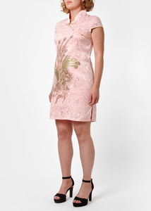 The Cheongsam or Qipao, is a feminine body-hugging dress with distinctive Chinese features of mandarin collar, side splits and hand stitched flower and knot frog fastenings. Manufactured in a subtle pink stretch cotton jacquard with a sequinned, gold embroidered peacock applique and gold piping. Invisible back zip
