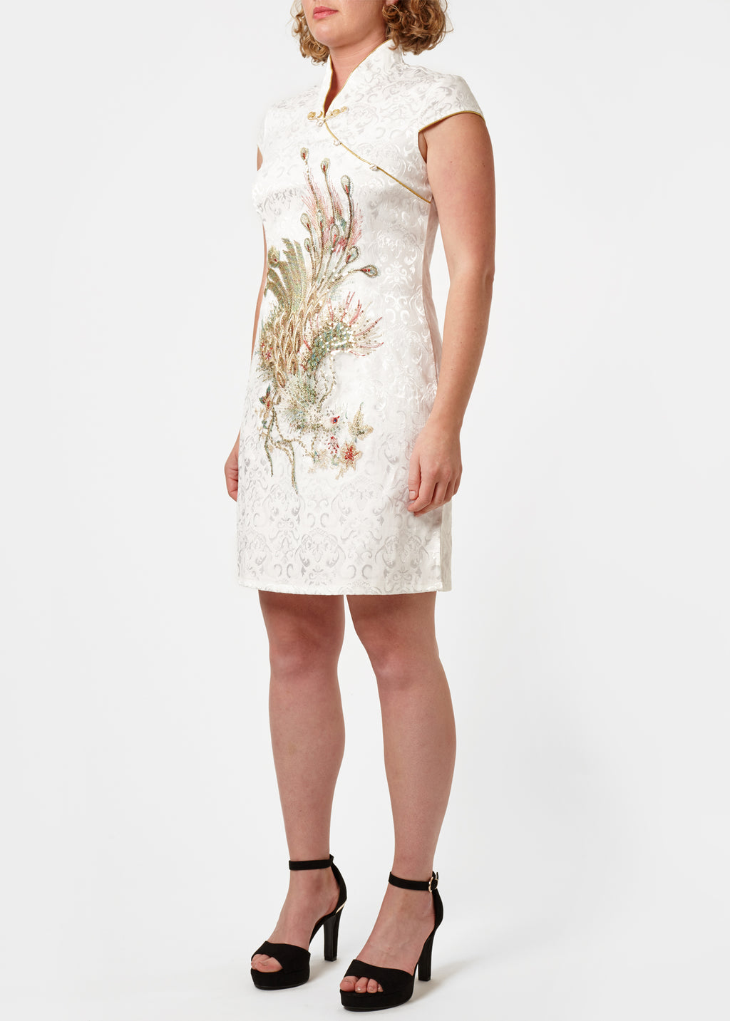 The Cheongsam or Qipao, is a feminine body-hugging dress with distinctive Chinese features of mandarin collar, side splits and hand stitched flower and knot frog fastenings. Manufactured in a classic ivory stretch cotton jacquard with a sequinned, gold embroidered peacock applique and gold piping. Invisible back zip