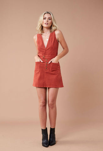 INDIE CORD PINNIE Made from a stretchy corduroy fabric, this mini dress boasts wide fixed straps, v-neckline, a 5-button front closure, and front patch pockets.  Designed with a plunging neckline with brass press studs, this dress is perfect for layering.