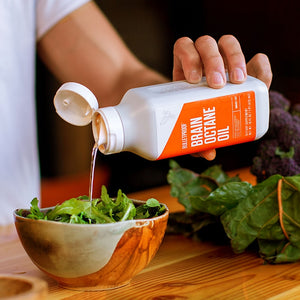 Bulletproof Brain Octane Oil being poured onto salad