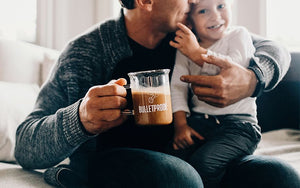 Man and child cuddling while man holds Bulletproof Beaker Mug full of Bulletproof Coffee