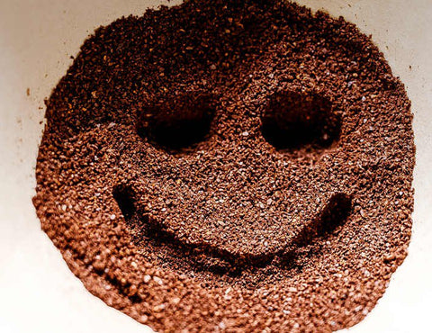 Smiley face drawn into coffee grounds