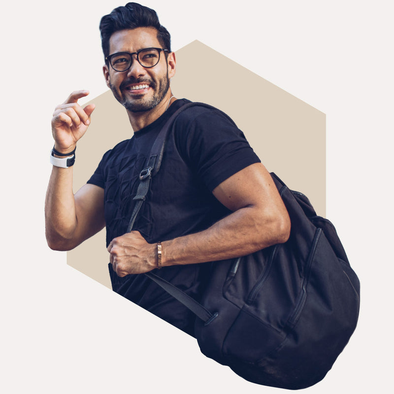 Man holding backpack and smiling