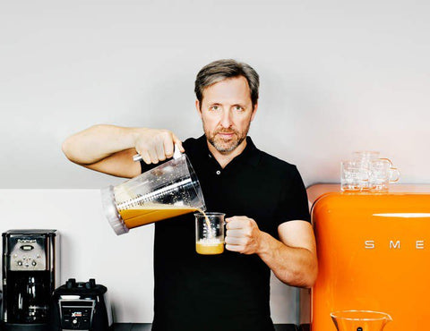 Dave Asprey pouring Bulletproof Coffee in beaker mug