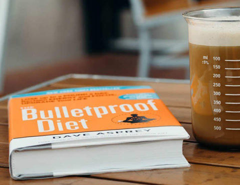 A copy of Dave Asprey's 'The Bulletproof Diet' next to a mug of Bulletproof Coffee