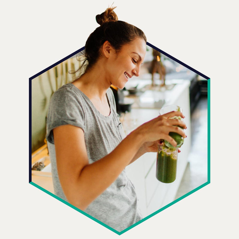 Woman holding green vegetable juice