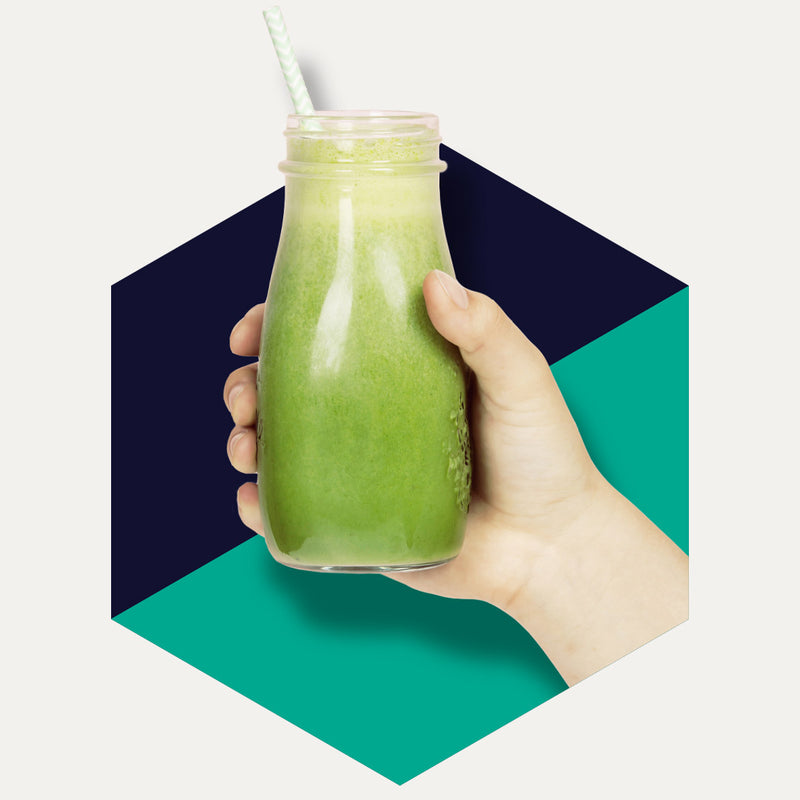 Hand holding green vegetable juice