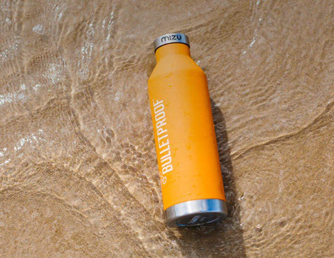 Bulletproof Insulated Bottle sitting on beach