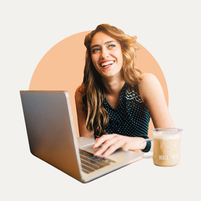 Woman on laptop drinking Bulletproof Coffee