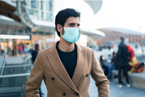 fashionable man only wearing face mask in the crowd