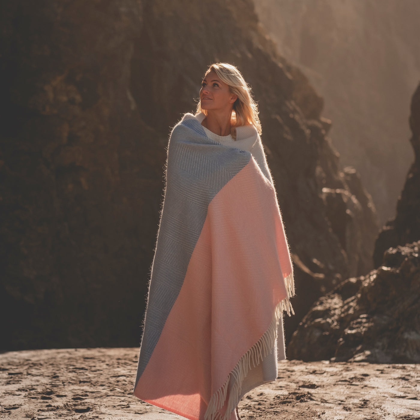 woman on beach with blue and pink blanket across shoulders