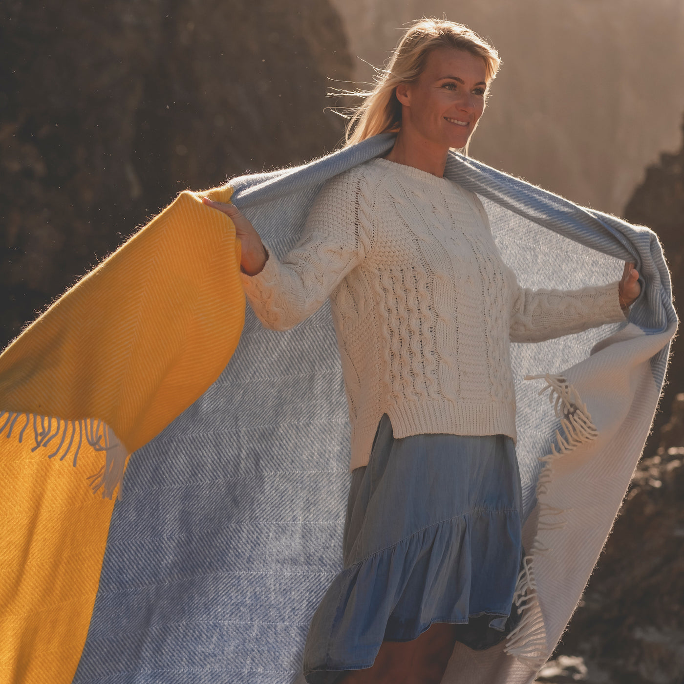 woman on beach with blue and yellow blanket across shoulders