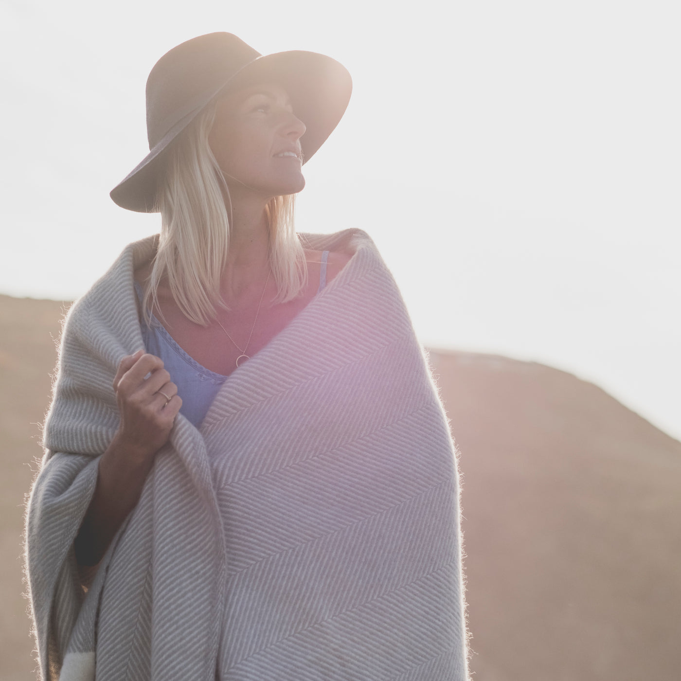 woman wrapped in a grey herringbone wool blanket on the coast