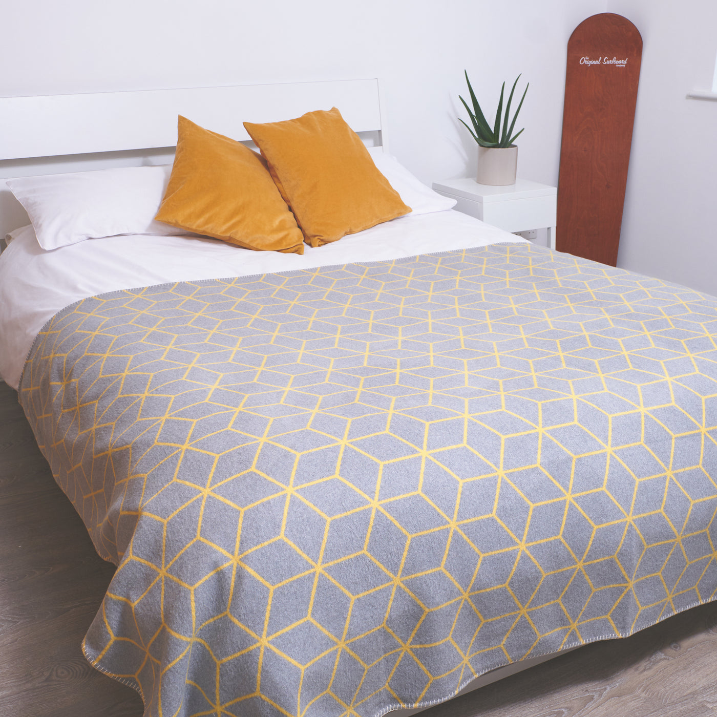 grey and yellow geometric blanket across a king size bed