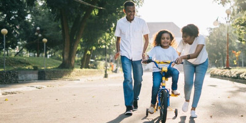 parents and kid on cycle