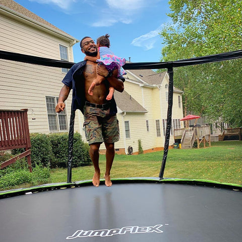 Dad and his child jumping and playing on a Jumpflex trampoline