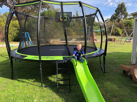 Jumpflex trampoline with toddler sitting on top of the Jumpflex slide