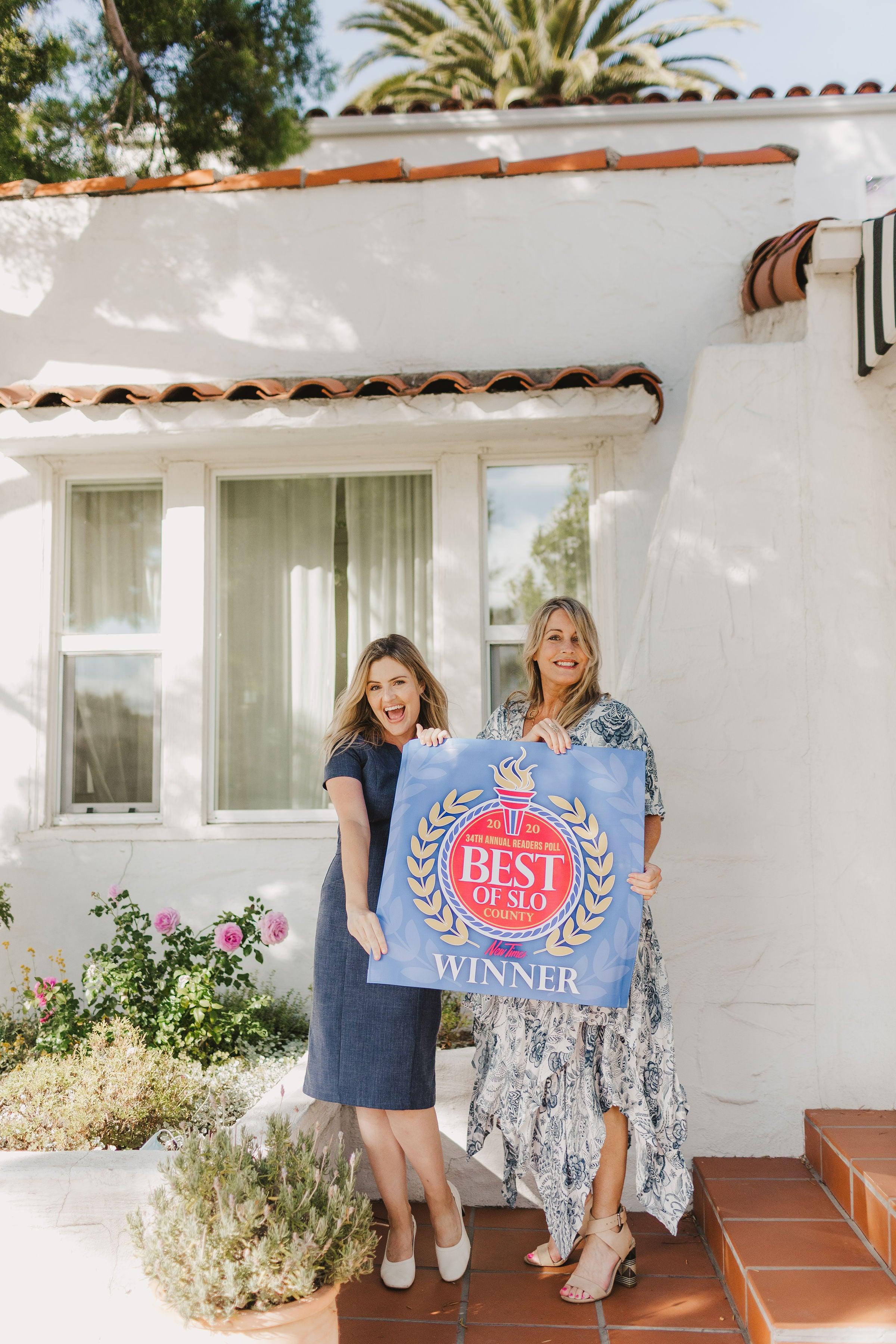 Mother daughter owners holding best of slo sign