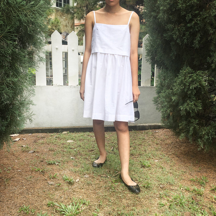 white cotton dress with crop top and skirt pockets with black flats and shades summer dress