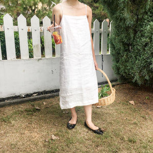 white ivory linen midi dress strappy for picnic and weekend brunch holding basket and juice summer dress french coast with black flats