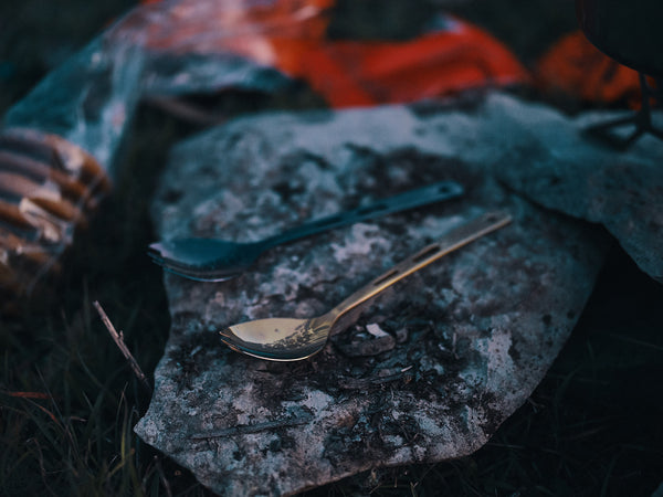 Two titanium spoons sitting on top of a rock