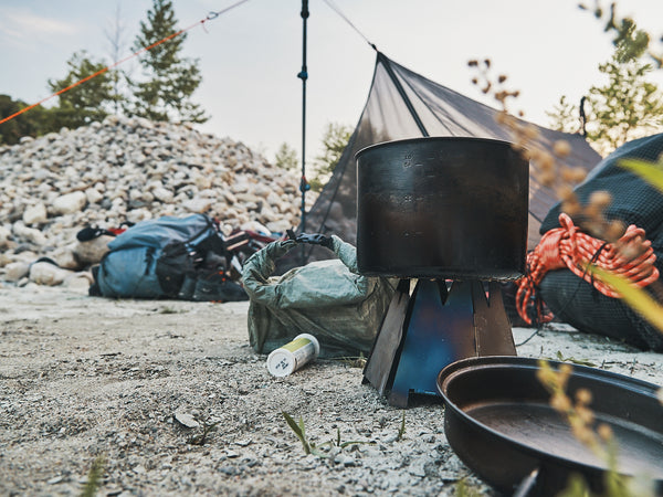 A titanium pot sitting on top of a lightweight stove in front of an assortment of ultralight backpacking equipment