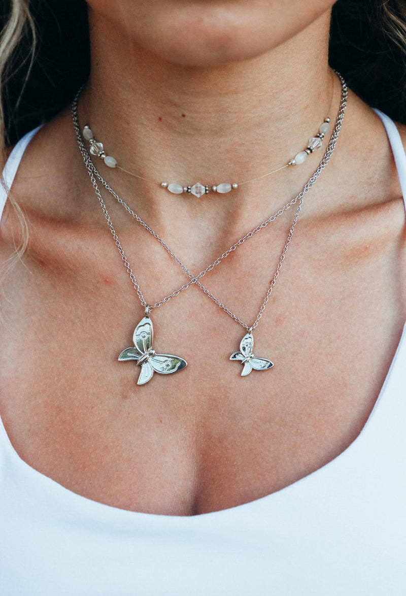 close up of girl wearing big and small butterfly necklaces with choker