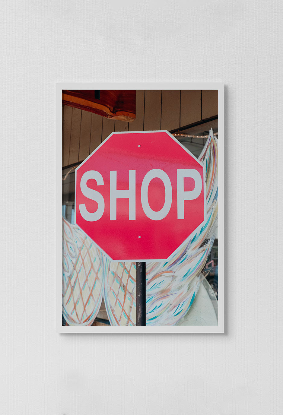 image of red sign with the words SHOP in white with wings in background in white frame on white wall.
