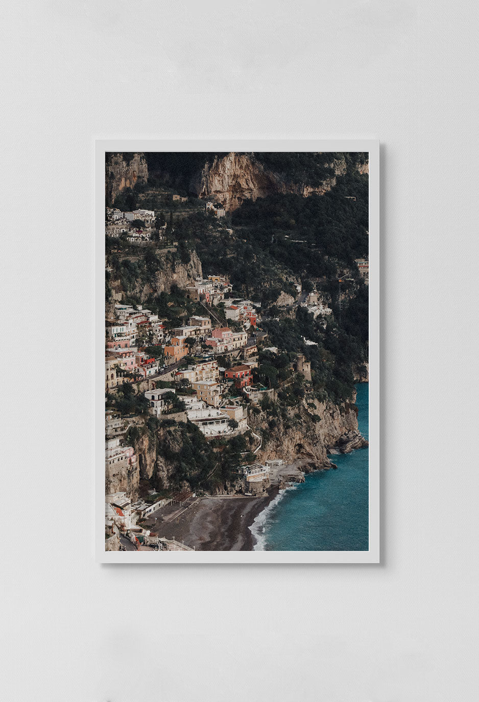 image of homes on beach looking over cliff side in white frame on white wall.