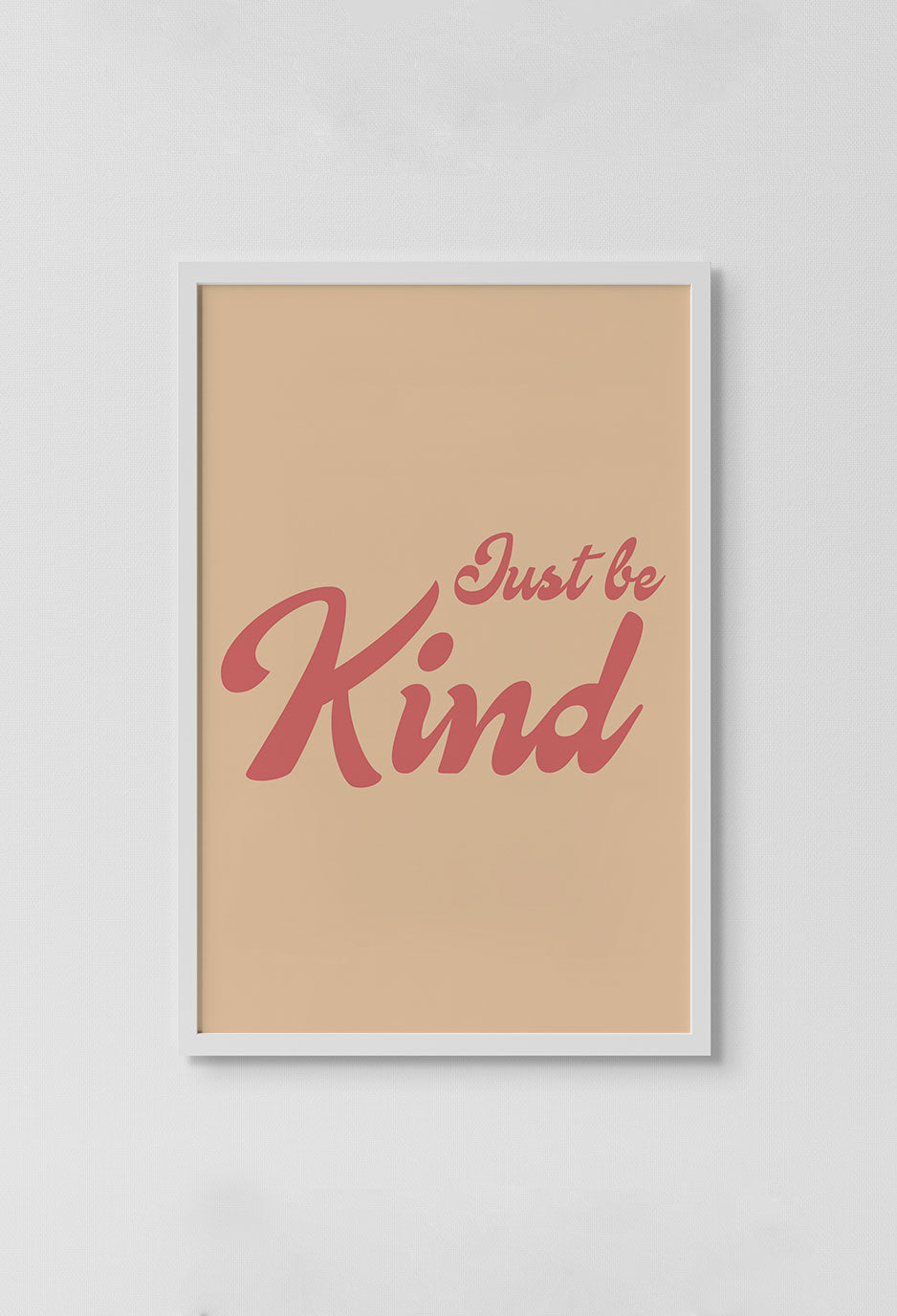image of orange print with just be kind words in pink in frame on white wall