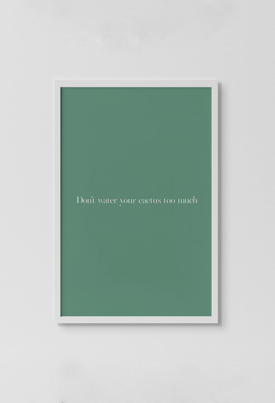 image of graphic if white letters that read dont water your cactus too much on dark green background in white frame on white wall.