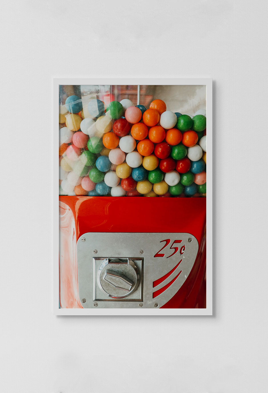 image of photo of red bubble gum machine with multi colored gum inside in white frame on white wall.