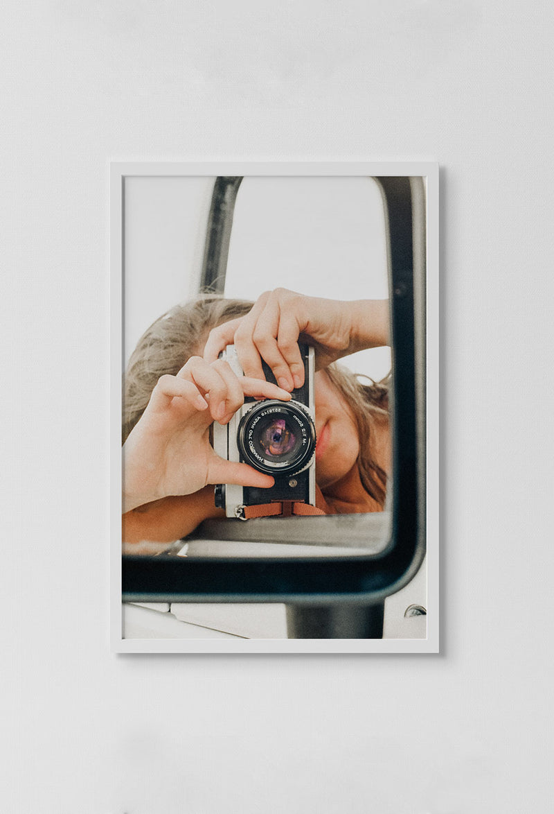image of photo of reflection of girl taking picture of herself in car mirror with camera in white frame on white wall.